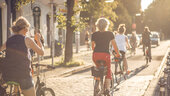 Group of cyclists cycling through Berlin in summer