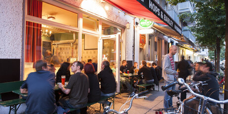People sitting outside of the micro brewery Hops & Barley in Berlin-Friedrichshain