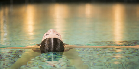 A woman relaxes in the pool of a day spa