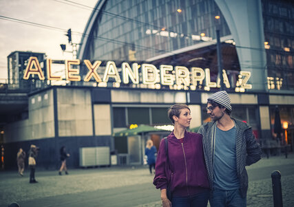 Young couple in front of the Alexanderplatz S-Bahn station at dusk