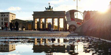 Brandenburg gate in Berlin: Reflection of the Brandenburg Gate in a puddle