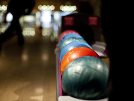 Colorful bowling balls on rack on bowling lane