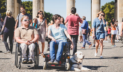 Two visitors in a wheel chair in front of the Brandenburger Tor
