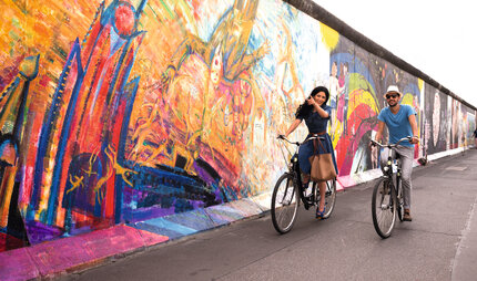 Berlin Touristen at the Berlin Wall with their bicycle