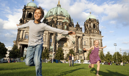 Boy and girl playing in front of Berliner Dom