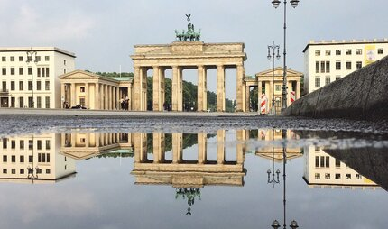 Brandenburg Gate reflected in a puddle at Pariser Platz