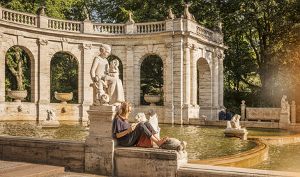 A woman reads at the fairytale fountain in the Volkspark Friedrichshain
